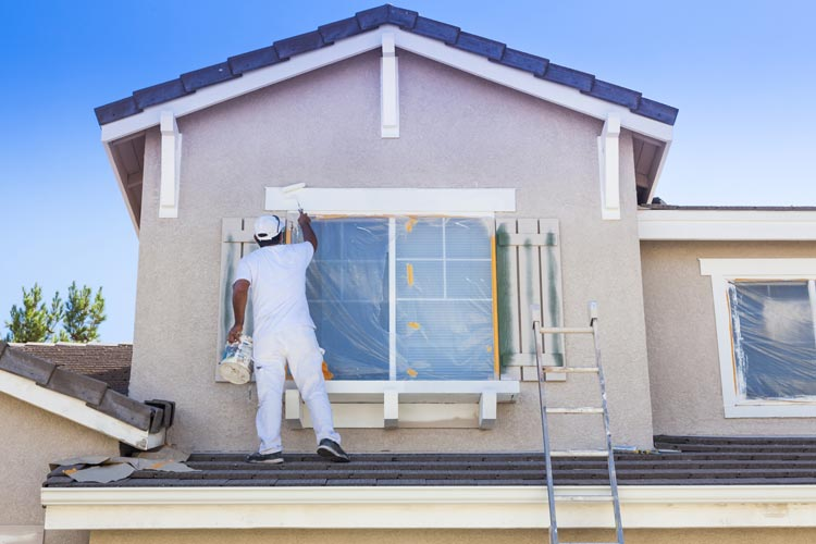 man painting exterior of home - window